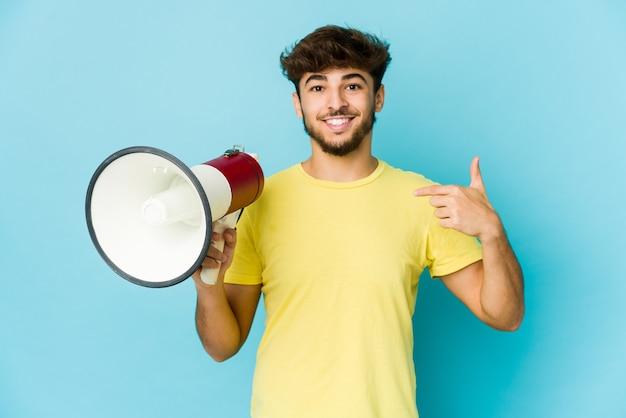 Joven árabe sosteniendo una persona megáfono apuntando con la mano a un espacio de copia de camisa, orgulloso y seguro