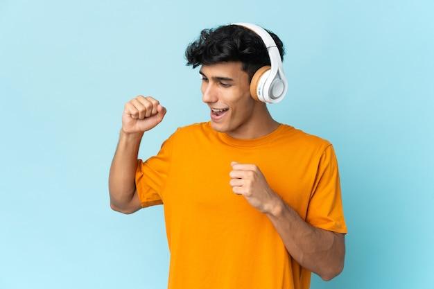 Joven argentino aislado en la pared escuchando música y bailando