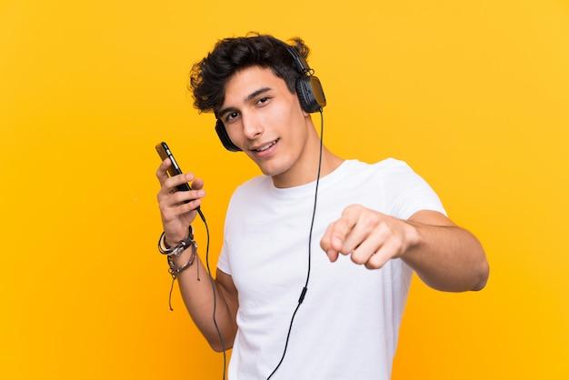 Joven argentino escuchando música con un móvil sobre pared amarilla aislada