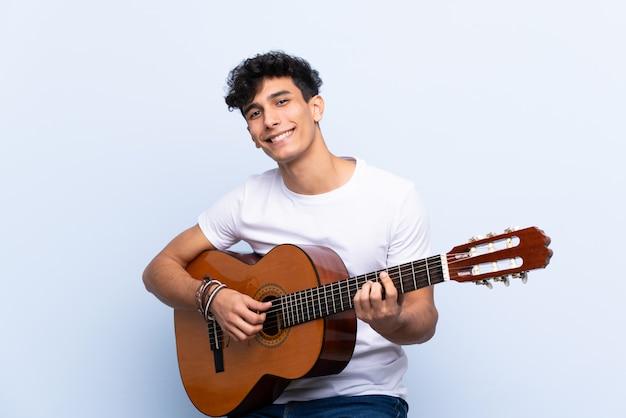 Joven argentino con guitarra sobre pared azul aislado sorprendido y apuntando con el dedo al lado