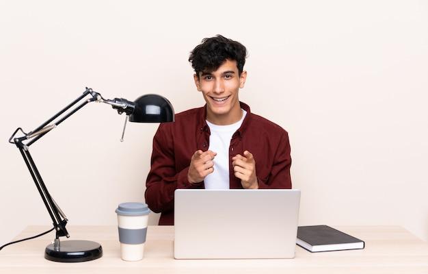 Joven argentino en una mesa con un portátil en su lugar de trabajo te señala con el dedo