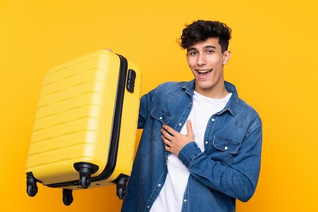Joven argentino sobre fondo amarillo aislado en vacaciones con maleta de viaje