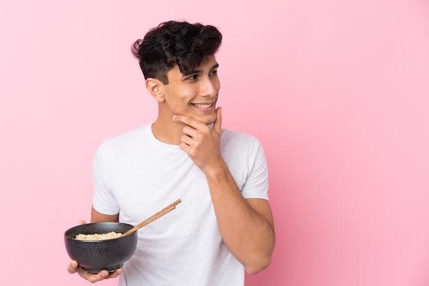 Joven argentino sobre pared blanca aislada pensando en una idea y mirando hacia un lado mientras sostiene un tazón de fideos con palillos