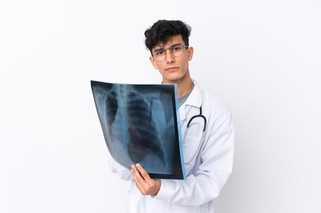 Joven argentino sobre pared blanca aislada vistiendo una bata de médico y sosteniendo una gammagrafía ósea