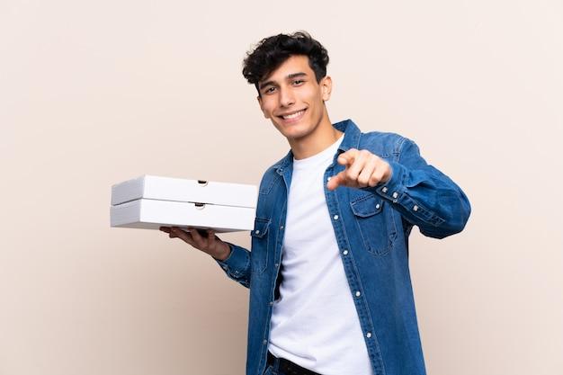 Joven argentino sosteniendo pizzas sobre una pared aislada te señala con una expresión segura