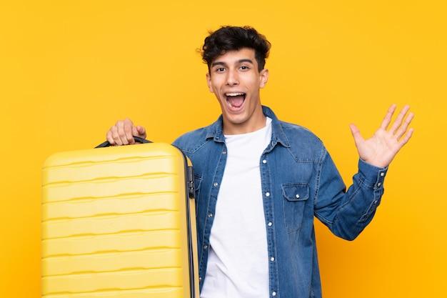 Joven argentino de vacaciones con maleta de viaje y sorprendido
