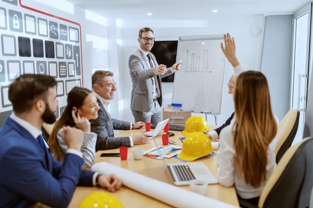 Joven arquitecto caucásico exitoso hablando de un nuevo proyecto y respondiendo preguntas. en el escritorio sus colegas se sientan y preguntan más sobre el proyecto.