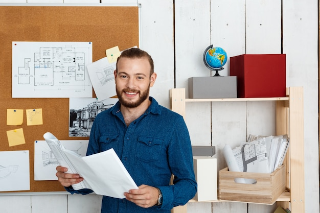 Joven arquitecto exitoso sonriendo, sosteniendo dibujos, de pie en la pared de la oficina