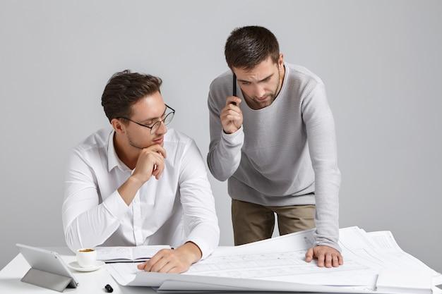 Joven arquitecto experimentado paciente viste camisa formal y gafas, enseña a su alumno o aprendiz masculino