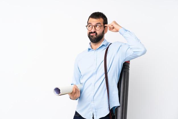 Joven arquitecto hombre con barba haciendo el gesto de locura poniendo el dedo en la cabeza