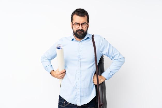 Joven arquitecto hombre con barba sobre pared blanca aislada enojado