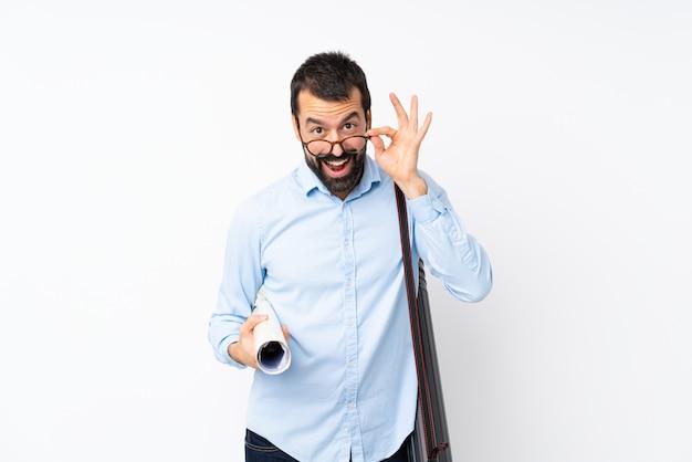 Joven arquitecto hombre con barba sobre pared blanca aislada con gafas y sorprendido