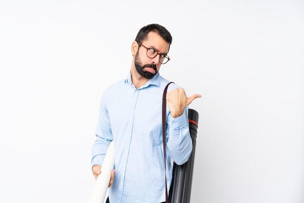 Joven arquitecto hombre con barba sobre pared blanca aislada infeliz y apuntando hacia el lado