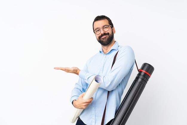 Joven arquitecto hombre con barba sobre la pared blanca aislada que presenta una idea mientras mira sonriente hacia