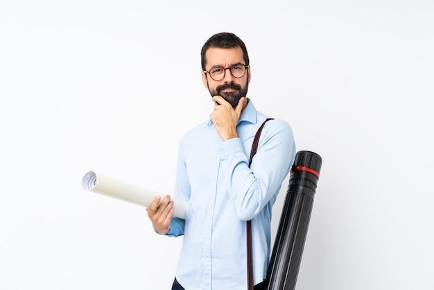 Joven arquitecto hombre con barba sobre pensamiento de pared blanca aislada