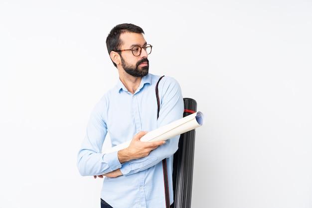 Joven arquitecto hombre con barba sobre retrato de pared blanca aislado