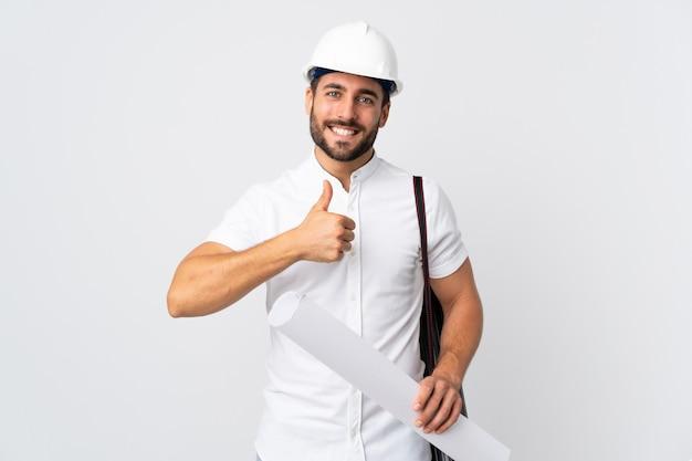 Joven arquitecto hombre con casco y sosteniendo planos aislados en la pared blanca dando un gesto de pulgares arriba
