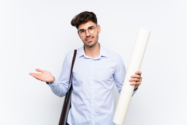 Joven arquitecto hombre sobre pared blanca aislada extendiendo las manos a un lado para invitar a venir