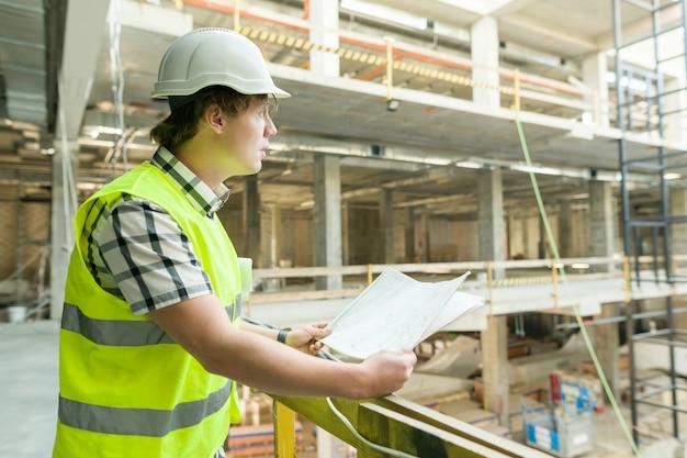 Joven arquitecto masculino en un sitio de construcción