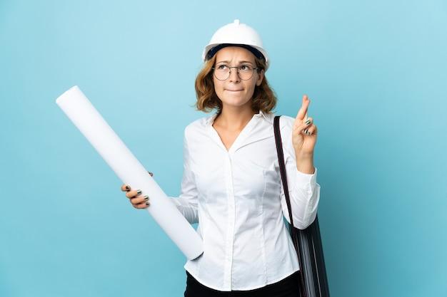 Joven arquitecto mujer georgiana con casco y sosteniendo planos sobre aislados con los dedos cruzados y deseando lo mejor
