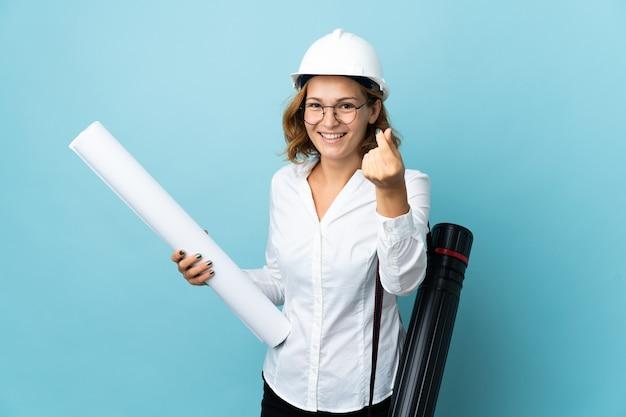 Joven arquitecto mujer georgiana con casco y sosteniendo planos sobre gesto de hacer dinero aislado