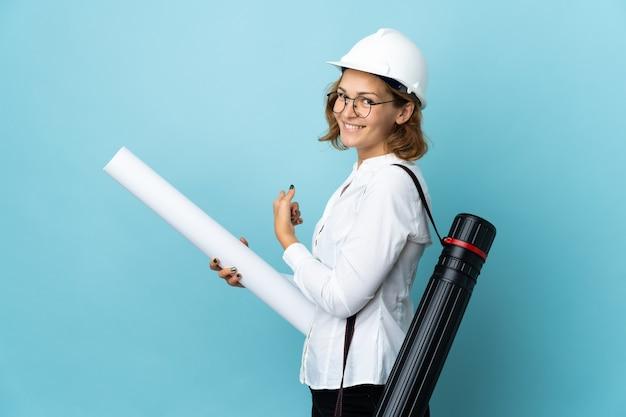 Joven arquitecto mujer georgiana con casco y sosteniendo planos sobre pared aislada apuntando hacia atrás