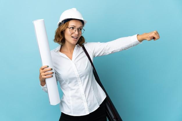 Joven arquitecto mujer georgiana con casco y sosteniendo planos sobre pared aislada dando un gesto de pulgar hacia arriba