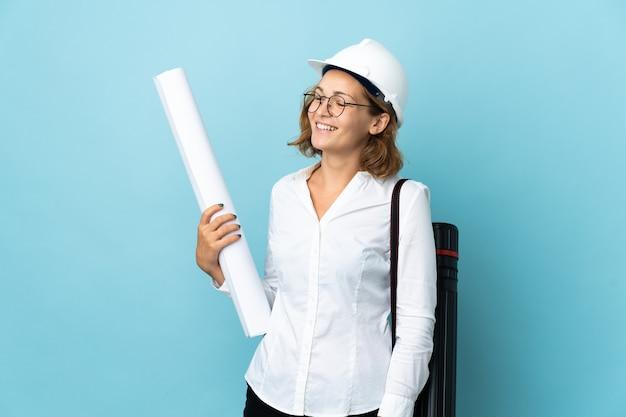 Joven arquitecto mujer georgiana con casco y sosteniendo planos sobre pared aislada mirando hacia el lado y sonriendo