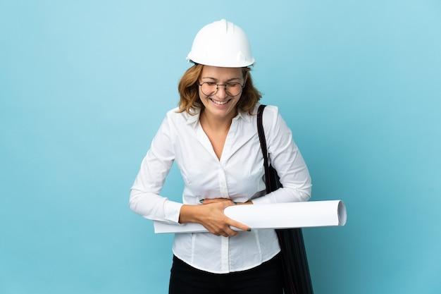 Joven arquitecto mujer georgiana con casco y sosteniendo planos sobre pared aislada sonriendo mucho