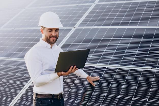 Joven arquitecto de pie junto a paneles solares haciendo diagnósticos en computadora