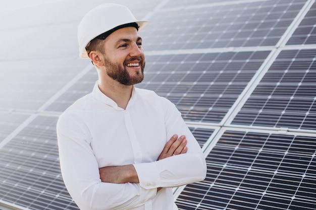 Joven arquitecto de pie junto a paneles solares