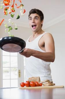 Joven arrojando verduras en sartén mientras cocina alimentos en la cocina