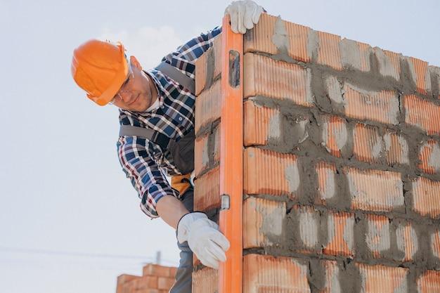 Joven artesano construyendo una casa