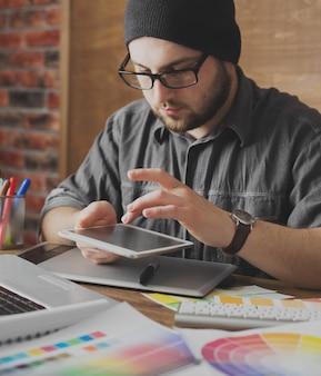 Joven artista creativo de diseño web con sombrero con tableta gráfica en la moderna oficina de loft