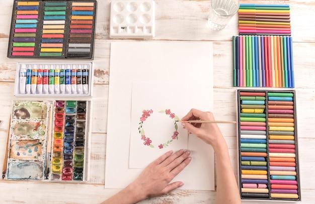 Joven artista dibujo patrón de flores con pintura de acuarela y pincel en el lugar de trabajo