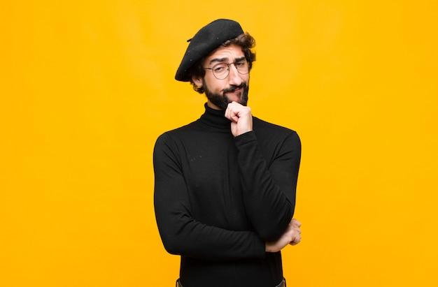 Joven artista francés hombre feliz y sonriente con la mano en la barbilla, preguntándose o haciendo una pregunta, comparando opciones contra la pared naranja