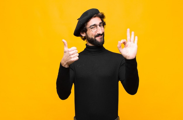 Joven artista francés hombre sintiéndose feliz, asombrado, satisfecho y sorprendido, mostrando gestos bien y pulgares arriba, sonriendo contra la pared naranja