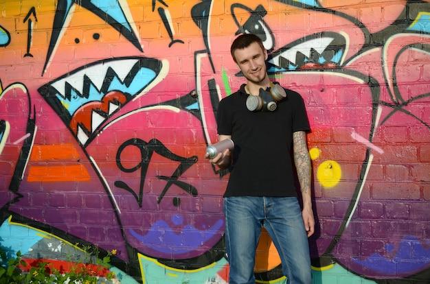 Joven artista de graffiti en camiseta negra con aerosol plateado puede cerca de coloridos graffiti