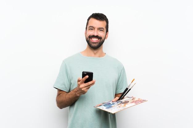 Joven artista hombre sosteniendo una paleta sobre fondo aislado enviando un mensaje con el móvil