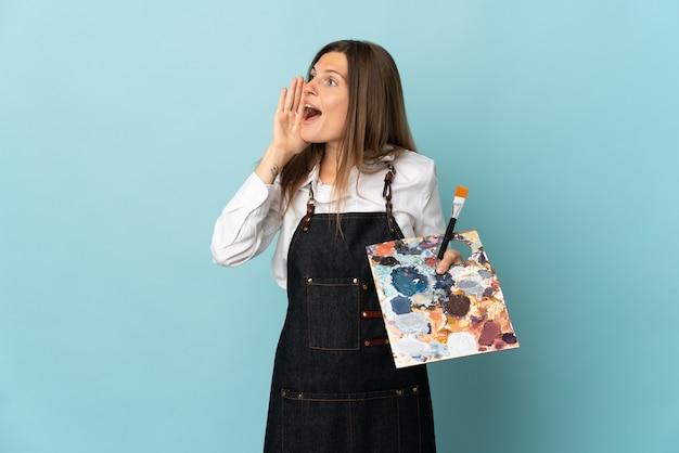 Joven artista mujer eslovaca aislada en la pared azul gritando con la boca abierta hacia el lado