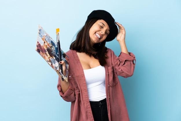 Joven artista mujer sosteniendo una paleta sobre espacio azul aislado sonriendo mucho