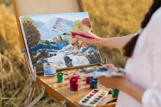 Joven artista pintando a mano en la naturaleza