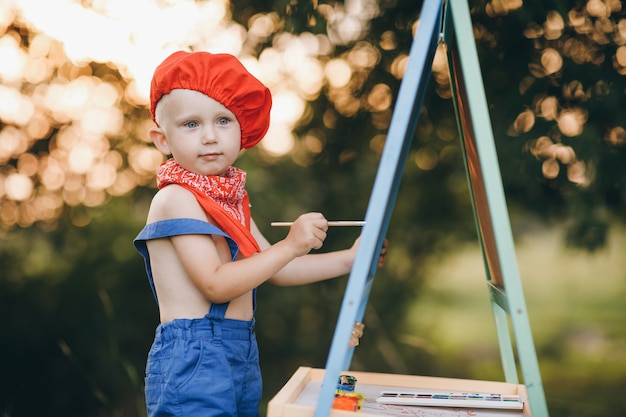Joven artista pintando un paisaje de verano. niño pintor sobre la naturaleza del artista dibuja