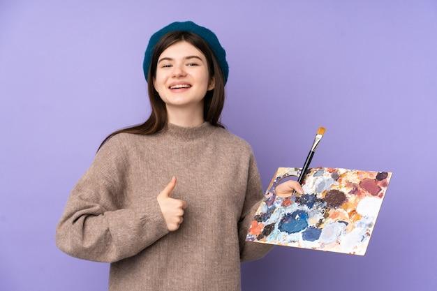 Joven artista sosteniendo una paleta sobre la pared púrpura con los pulgares hacia arriba porque algo bueno ha sucedido
