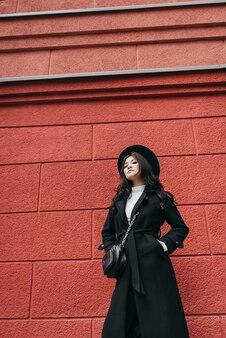 Joven asiática en abrigo oscuro y sombrero de pie delante de la pared roja, retrato de paseo de otoño