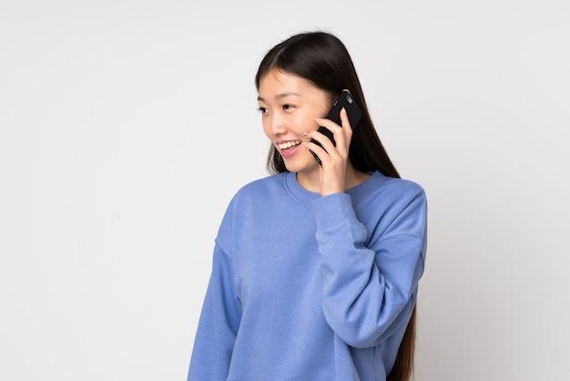 Joven asiática aislada en la pared manteniendo una conversación con el teléfono móvil con alguien
