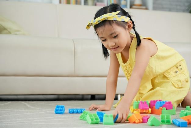 Joven asiática arrodillada en el piso en casa y jugando con coloridos bloques de construcción