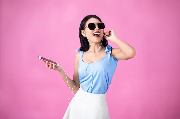 Joven asiática en auriculares escuchando música y bailando