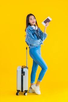 Joven asiática con bolsa de equipaje y pasaporte