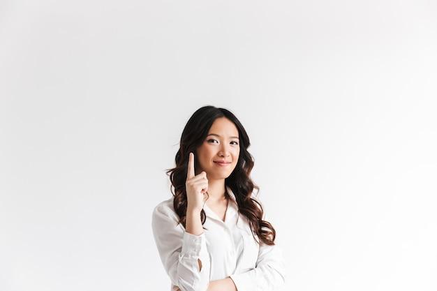 Joven asiática con cabello largo y oscuro con una hermosa sonrisa y apuntando con el dedo hacia arriba